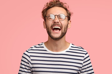 Overjoyed guy laughs joyfully as hears something funny, can`t stop happiness, has carefree lifestyle, wears spectacles, balck and white striped sweater, stands over pink background. Positive emotions
