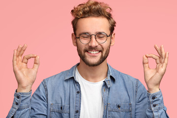 Portrait of cheerful satisfied male with stubble, stands in mudra sign, keeps eyes shut, has positive smile, stands indoor against pink background, wears jean shirt. People and body language concept