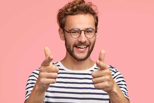 Positive unshaven male points at you, has happy expression, curly hair, bristle, expresses his choice, wears striped clothes, isolated on pink background. Man does finger gun gesture. You are my type