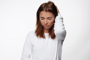 Troubled beautiful young female with dark red hair, keeps hand on back of  head, wears white shirt, isolated over white concrete background. Pretty hipster woman has some problems with boss or work.