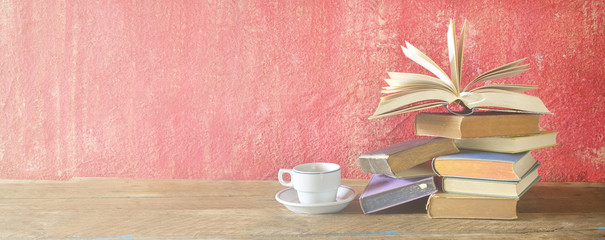 Open Book on a pile of old books and a cup of coffee, panorama, good copy space