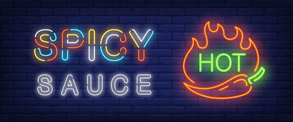 Spicy sauce, hot neon text with chili pepper and fire flames. Cafe or restaurant advertisement design. Night bright neon sign, colorful billboard, light banner. Vector illustration in neon style.