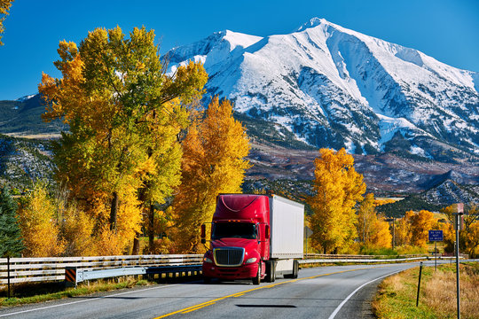 Red truck on highway in Colorado at autumn