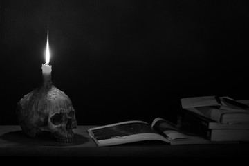 Skull with candle on head which has candlelight lighting for read and learn on the wooden plank in dark room