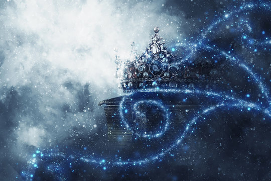 mysteriousand magical image of old crown and book over gothic black background. Medieval period concept.