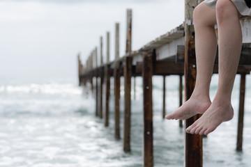 Leg of human sit on the sea bridge at koh kood island thailand
