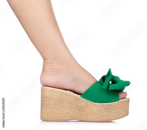 05480bce7f2 Beautiful female leg in green wedge sandals isolated on white background