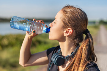 Sport and fitness. Young woman training outdoor with bottle of water at sunrise.