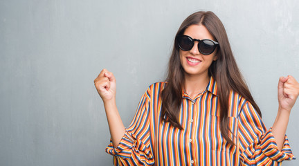 Young brunette woman over grunge grey wall wearing big sunglasses screaming proud and celebrating victory and success very excited, cheering emotion