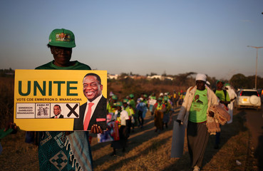 A supporter of ZANU PF poses for a photograph after attendening the final rally at the NationaLsports stadium in Harare