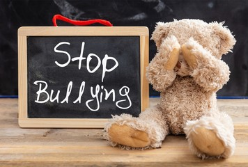 Teddy bear covering eyes and stop bullying text on a blackboard