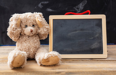 Teddy bear covering ears and a blank blackboard, space for text