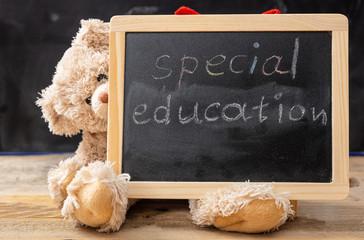 Teddy bear hiding behind a blackboard. Special education text drawing on the blackboard