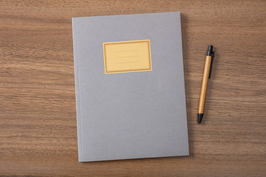 Grey school notebook or diary, old fashioned, on wooden desk, blank label, space for text, top view