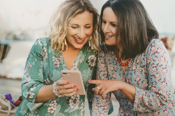 Two beautiful middle-aged smiling women look at the smartphone. A blonde woman and the other brunette flip through the photos on the cell phone.