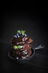 chocolate pancakes for breakfast with blueberries, dark photo. Homemade baking