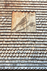 Wooden roof tiles and the image of a bird on the roof of a medieval tenement house in the city of Troyes.