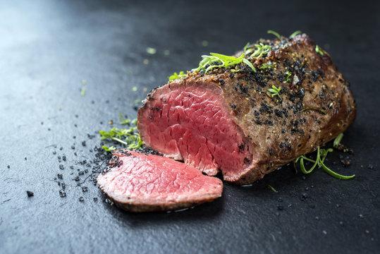 Traditionelles Barbecue dry aged Wagyu Rinder Filet Steak mariniert mit Kräuter und Gewürzen als closeup auf einem schwarzen Board