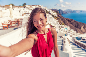 Fototapete - Travel vacation tourist girl selfie photo with phone on Santorini holiday. Happy asian woman in Oia smiling taking self-portrait picture with smartphone on summer vacation in Greece destination.