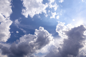 cloudscape with blue sky and shining sun