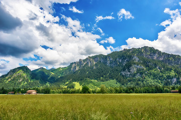 Idyllic landscape in the Alps with green meadows and clouds