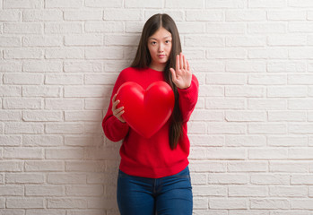 Young Chinese woman in love over brick wall holding red heart with open hand doing stop sign with serious and confident expression, defense gesture