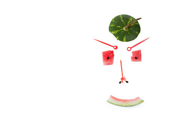 Funny Face person made of a hat from watermelon, cubes of watermelon and sunflower seeds. Top view. White background, horizontal shot. The place for an inscription