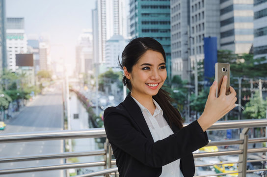 young asian business woman smiling wearing modern black suit video conference with mobile phone in building city background, network technology, internet, digital financial and investment concept