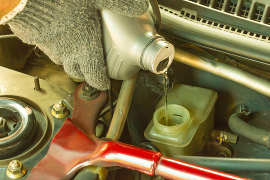 Car maintenance service, Close up of Auto mechanic pouring new brake fluid to car engine.
