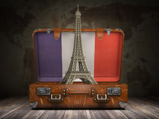 Trip to Paris. Travel or tourism to France concept. Eiffel tower andvintage suitcase with flag of France on the map of world background