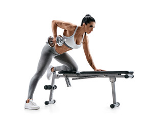 Fitness woman doing exercise with dumbbell leaning on sports bench. Photo of attractive latin woman in fashionable sportswear isolated on white background. Strength and motivation