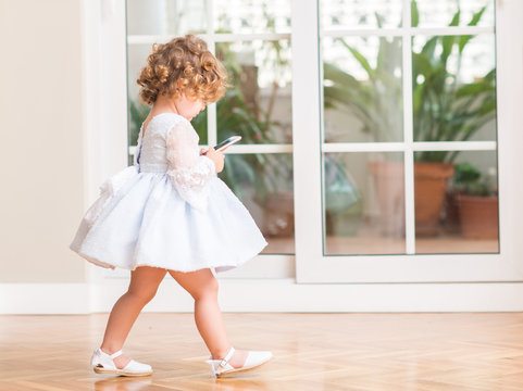 Beautiful blonde child in a dress walking playing with smartphone at home.