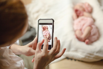 A woman holding a smartphone and takes a picture of a newborn baby girl sleeping on a white blanket. Selective focus.