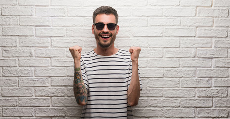 Young adult man wearing sunglasses standing over white brick wall celebrating surprised and amazed for success with arms raised and open eyes. Winner concept.