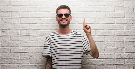Young adult man wearing sunglasses standing over white brick wall showing and pointing up with finger number one while smiling confident and happy.