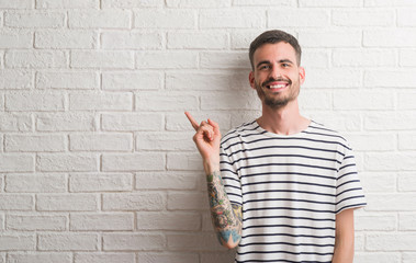 Young adult man standing over white brick wall very happy pointing with hand and finger to the side