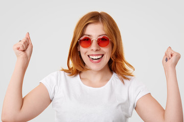Happy successful ginger young female keeps clenched fists raised, has toothy smile, celebrates successful day, dressed in casual clothing, isolated over white background. Body language concept