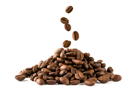 A bunch of coffee beans and falling coffee beans on a white background. Isolated.