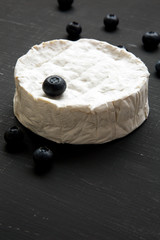 Camembert cheese with blueberries on black background. Side view. Closeup.