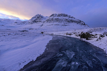Frozen river near mountains in winter. Winter landscapes and nature of Iceland.