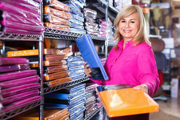Mature female customer choosing color bedsheet in textile store