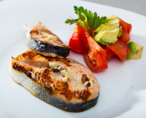 Grilled salmon with tomatoes, avocado on white dish