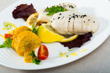 Codfish steamed and served with boiled corn, herbs and lemon