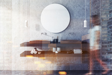 Double sink and mirror in concrete bathroom, woman