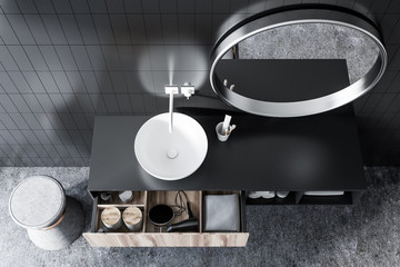 Top view of a sink in black tile bathroom