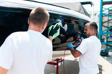 Boat maintenance - Two men polishing boat. Selective focus.