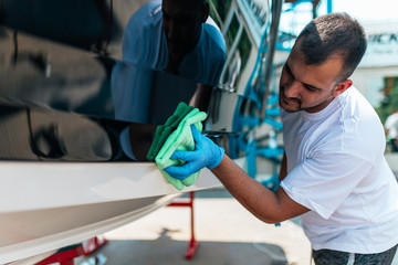 Boat maintenance - A man cleaning boat with cloth.