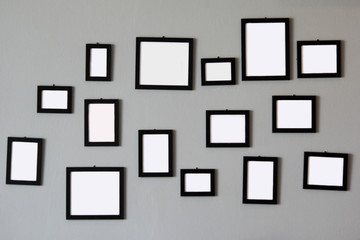 pile of empty wooden picture frames on wall