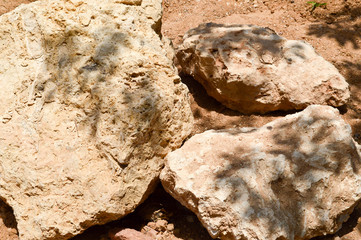 Texture of a stone wall, roads from large round and oval stones with sand with seams of natural old yellow black brown. The background.