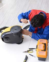 Man repairman repairing vacuum cleaner at service center